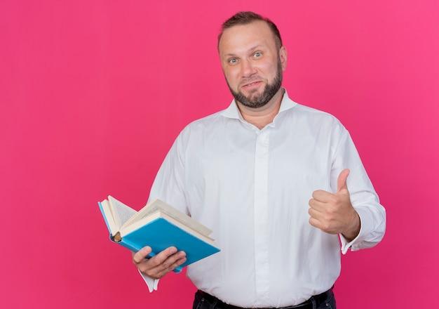 Бородатый мужчина в белой рубашке держит открытую книгу улыбается, показывая пальцы вверх, стоя над розовой стеной