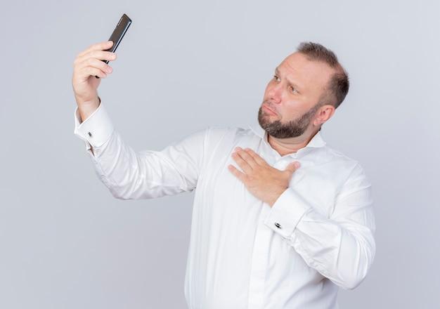 白い壁の上に立っている胸に手をつないでビデオ通話を持っているスマートフォンを持っている白いシャツを着ているひげを生やした男