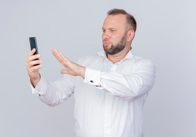 白い壁の上に立っている防衛ジェスチャーを作る画面を見ているビデオ通話を持っているスマートフォンを持っている白いシャツを着ているひげを生やした男