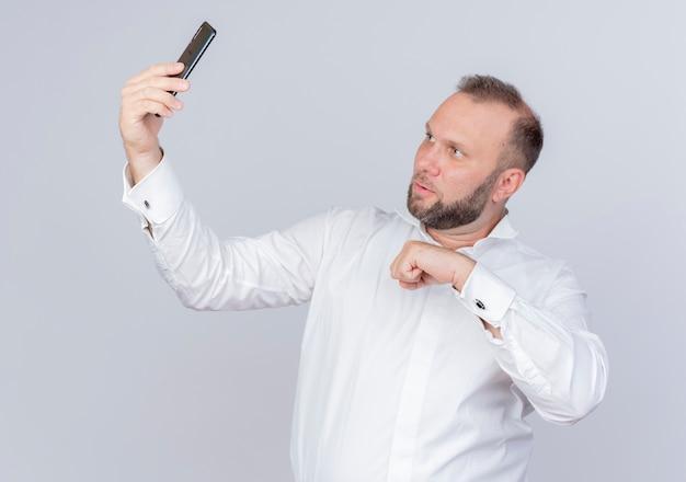 白い壁の上に立っている真面目な顔で画面を見ているビデオ通話を持っているスマートフォンを持っている白いシャツを着ているひげを生やした男