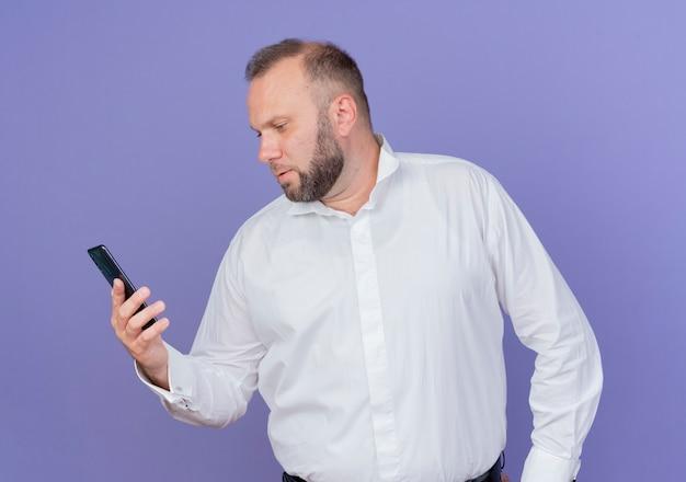 파란색 벽 위에 서 심각한 얼굴로 화면을보고 스마트 폰을 들고 흰 셔츠를 입고 수염 난된 남자