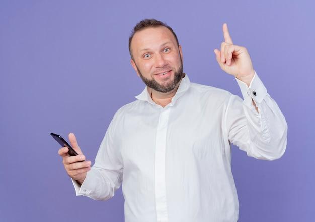 Бородатый мужчина в белой рубашке держит смартфон, выглядит счастливым и удивленным, показывая указательный палец с новой идеей, стоящим над синей стеной