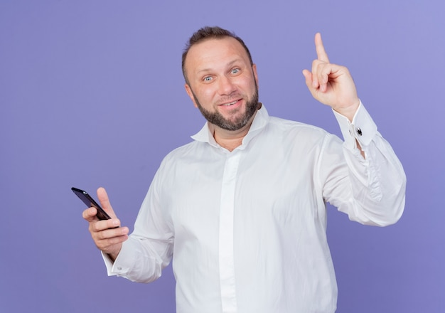 Bearded man wearing white shirt holding smartphone looking  happy and surprised showing index finger having new idea standing over blue wall