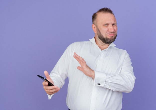 Bearded man wearing white shirt holding smartphone making defense gesture with hand looking with disgusted expression standing over blue wall