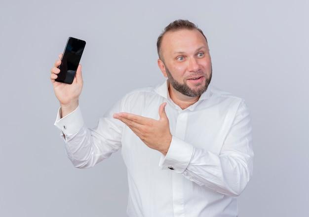 흰 벽에 팔을 행복하고 긍정적으로 제시하는 스마트 폰을 들고 흰 셔츠를 입고 수염 난된 남자