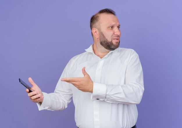 Бородатый мужчина в белой рубашке держит смартфон с рукой, смотрящей в сторону, стоя у синей стены