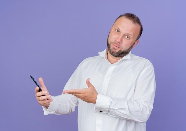 Бородатый мужчина в белой рубашке держит смартфон с растерянной рукой, стоя у синей стены