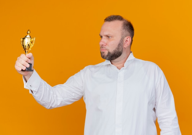 Bearded man wearing white shirt holding trophy looking at it with serious face standing over orange wall