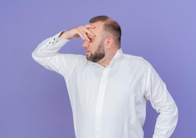 파란색 벽 위에 서 실수로 머리에 손으로 혼란 스 러 워 보이는 흰색 셔츠를 입고 수염 난된 남자