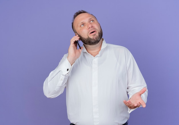 Uomo barbuto che indossa una camicia bianca che osserva da parte perplesso mentre parla al telefono cellulare in piedi sopra la parete blu