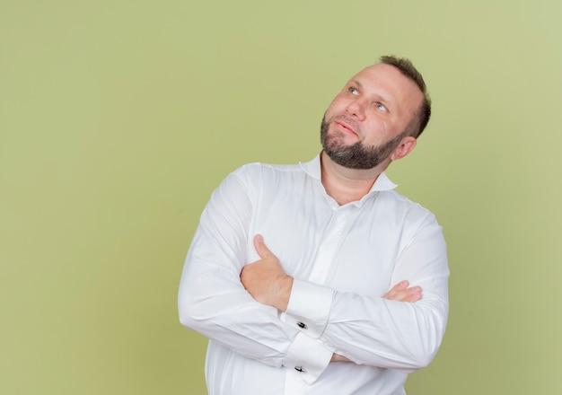 가벼운 벽에 옆으로 서있는 흰색 셔츠를 입고 수염 난된 남자