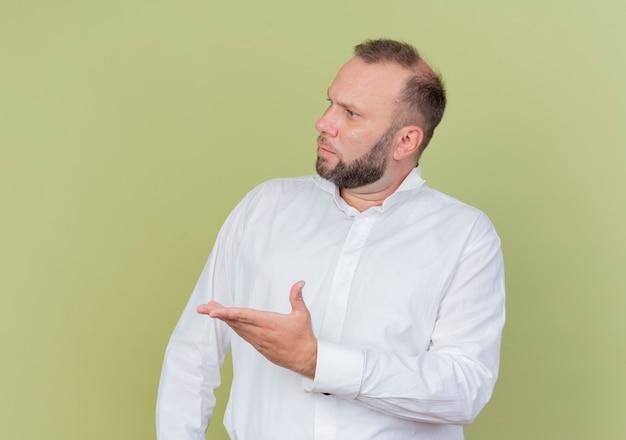 Бородатый мужчина в белой рубашке смотрит в сторону с вытянутой рукой и недовольно спрашивает, стоя у светлой стены