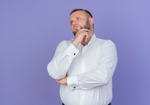 Бородатый мужчина в белой рубашке смотрит в сторону с задумчивым выражением лица, держа руку на подбородке, думая, стоя над синей стеной