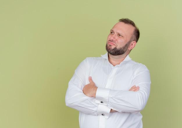 Бородатый мужчина в белой рубашке смотрит в сторону с серьезным лицом, скрестив руки на груди, стоит над светлой стеной