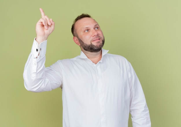 가벼운 벽 위에 서있는 새로운 좋은 아이디어를 갖는 검지 손가락을 보여주는 얼굴에 미소로 옆으로 보이는 흰 셔츠를 입고 수염 난 남자