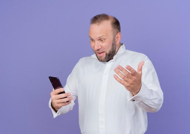 파란색 벽 위에 행복하고 흥분 서 웃는 손으로 몸짓 그의 스마트 폰 화면을보고 흰 셔츠를 입고 수염 난된 남자