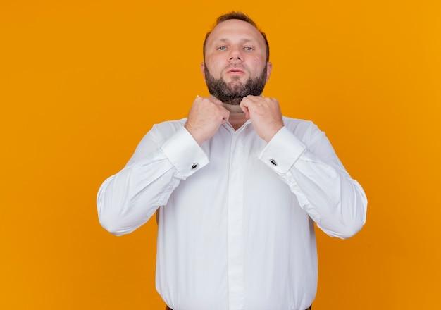 오렌지 벽 위에 서있는 그의 칼라를 고정하는 자신감을 찾고 흰 셔츠를 입고 수염 난된 남자