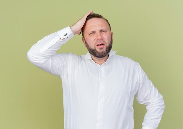 明るい壁の上に立っている間違いのために彼の頭の手で混乱しているように見える白いシャツを着たひげを生やした男