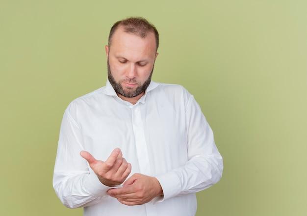 明るい壁の上に立っているカフスボタンを固定して見下ろしている白いシャツを着ているひげを生やした男