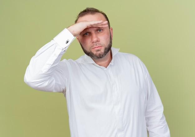 明るい壁の上に立っている頭の上に手で遠くを見ている白いシャツを着ているひげを生やした男
