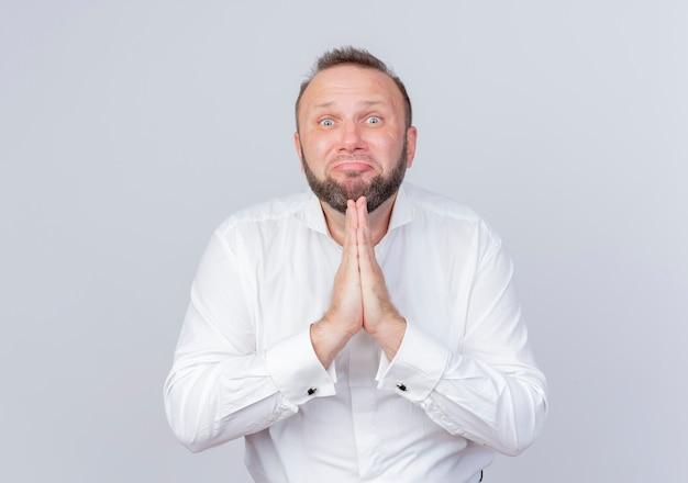 Uomo barbuto che indossa una camicia bianca che guarda le mani insieme come pregare e implorare con espressione di speranza in piedi sul muro bianco
