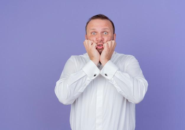 흰 셔츠를 입고 수염 난된 남자가 파란색 벽 위에 서있는 앤 긴장감을 강조했다.