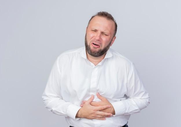 Uomo barbuto che indossa una camicia bianca che non sembra stare bene toccando la sua pancia che ha dolore in piedi sul muro bianco