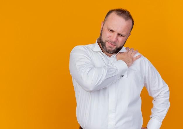 オレンジ色の壁の上に立っている痛みを感じて彼の肩に触れて気分が悪いように見える白いシャツを着たひげを生やした男