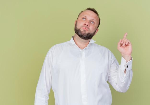 明るい壁の上に立っている真面目な顔で人差し指を見せて見上げる白いシャツを着たひげを生やした男