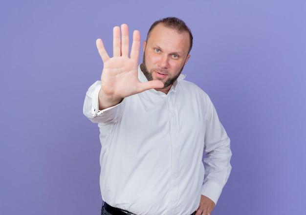 Бородатый мужчина в белой рубашке смотрит с серьезным лицом, делая знак остановки с рукой, стоящей над синей стеной