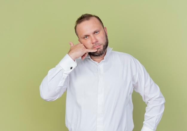 白いシャツを着たひげを生やした男が明るい壁の上に立っている真面目な顔でジェスチャーを呼んで