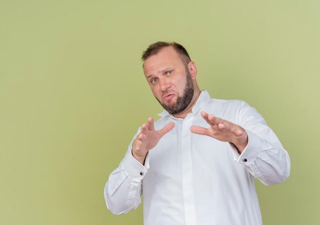 白いシャツを着たひげを生やした男が明るい壁の上に立って手を差し伸べる防衛ジェスチャー