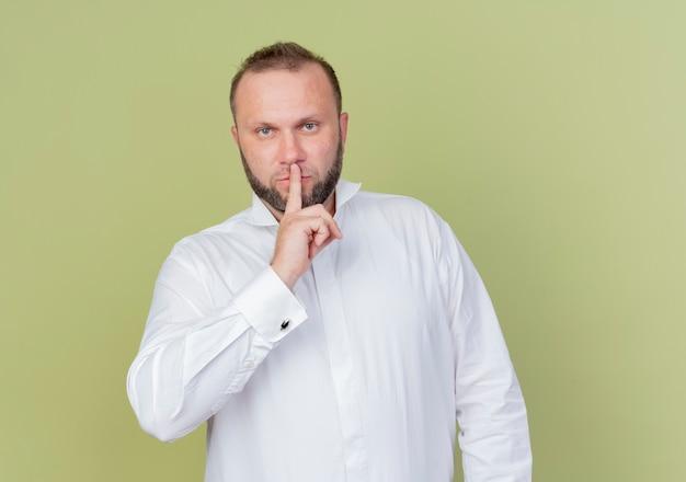 明るい壁の上に立っている唇に指で沈黙のジェスチャーをする白いシャツを着ているひげを生やした男