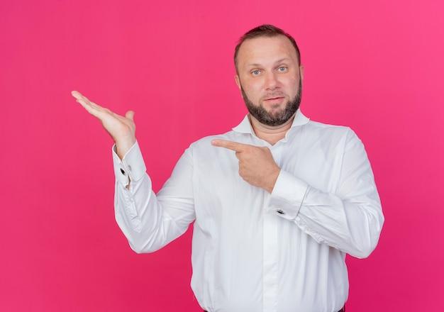 Бородатый мужчина в белой рубашке представляет что-то с рукой, указывающей пальцем в сторону, стоящей над розовой стеной