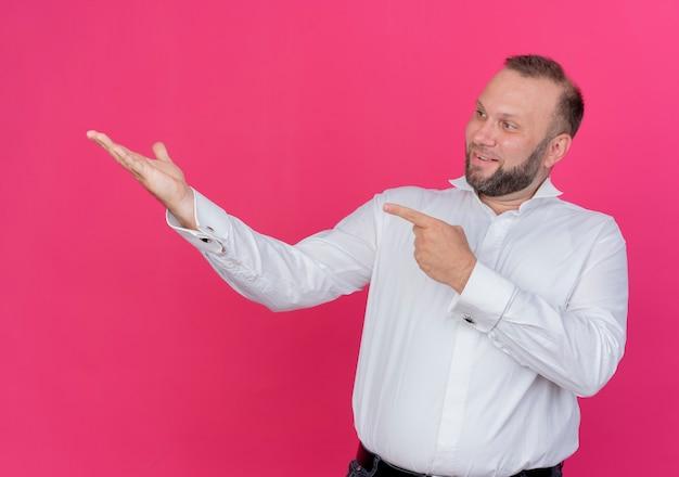 Бородатый мужчина в белой рубашке представляет что-то с рукой, указывающей на нее указательным пальцем, улыбаясь, стоя над розовой стеной