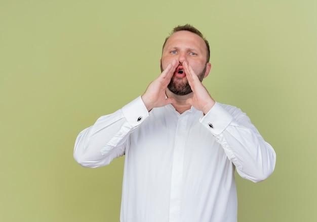 明るい壁の上に立っている口の近くで叫んだり、手を呼んだりする白いシャツを着たひげを生やした男