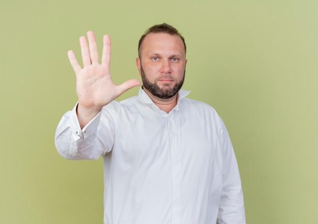 白いシャツを着たひげを生やした男が明るい壁の上に立っている真面目な顔で見ている5番の指で上向き