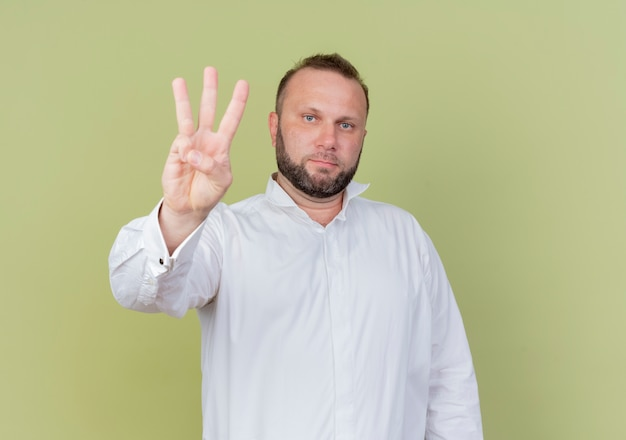 明るい壁の上に立っている真面目な顔で見ている3番目の指で上向きに見せて白いシャツを着ているひげを生やした男