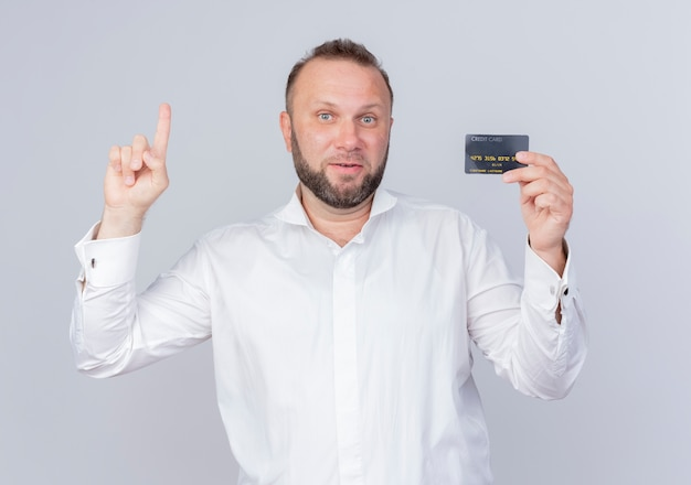 Bearded man wearing white shirt showing credit card showing index finger smiling with happy face having new idea standing over white wall
