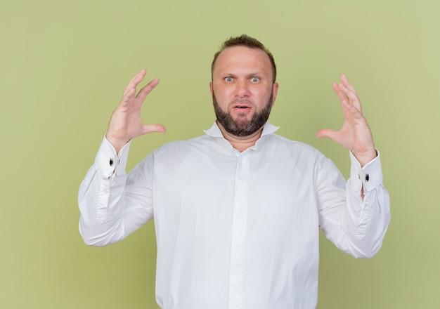 가벼운 벽 위에 서있는 대형 제스처 측정 기호를 보여주는 흰색 셔츠를 입고 수염 난된 남자