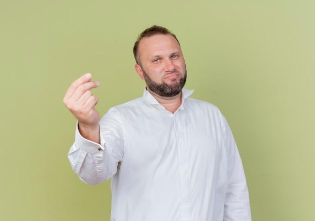 Uomo barbuto che indossa una camicia bianca che mostra il gesto di denaro strofinando le dita in piedi sopra la parete leggera