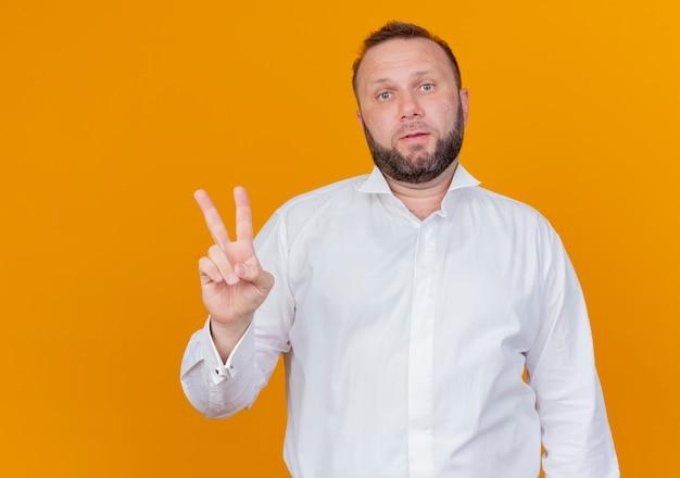주황색 벽에 두 번째 서를 보여주는 흰색 셔츠를 입고 수염 난된 남자