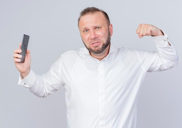 흰 벽에 자신감이 서있는 팔뚝을 보여주는 스마트 폰 떨림 주먹을 보여주는 흰 셔츠를 입고 수염 난된 남자