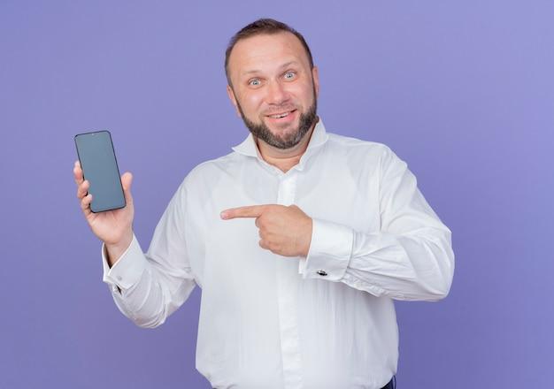 Uomo barbuto che indossa una camicia bianca che mostra lo smartphone pointign con il dito indice a sorridere in piedi sopra la parete blu