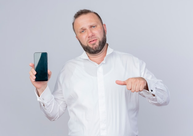 Bearded man wearing white shirt showing smartphone pointing with thumb at it looking displeased standing over white wall