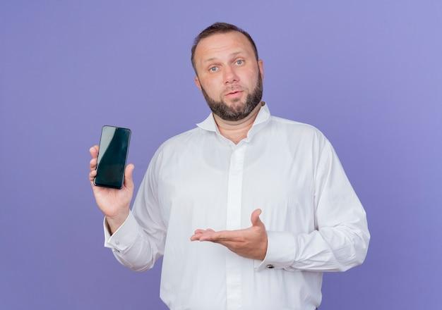 Бородатый мужчина в белой рубашке показывает смартфон с рукой, стоящей над синей стеной