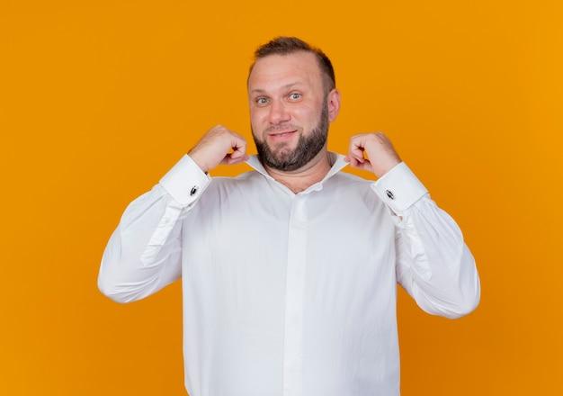 흰색 셔츠를 입고 수염 난된 남자 오렌지 벽 위에 서있는 그의 칼라 서 자신감 웃고