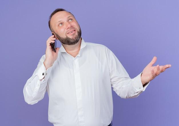 파란색 벽 위에 서있는 휴대 전화에 얘기하는 동안 손으로 몸짓 웃고 흰 셔츠를 입고 수염 난된 남자