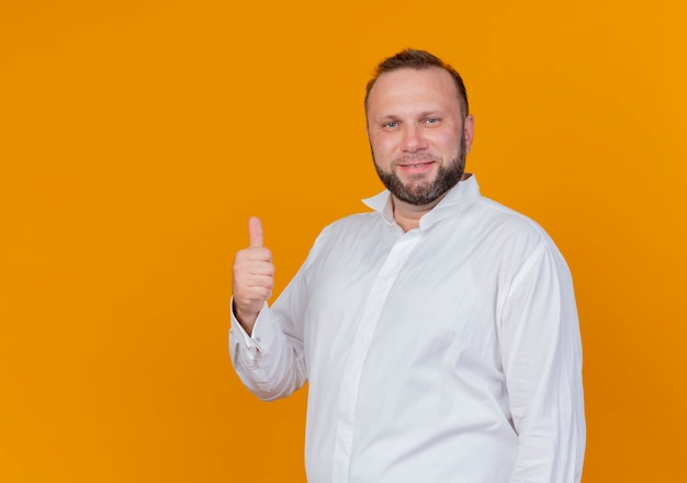 オレンジ色の壁の上に立って親指を見せて笑って白いシャツを着ているひげを生やした男