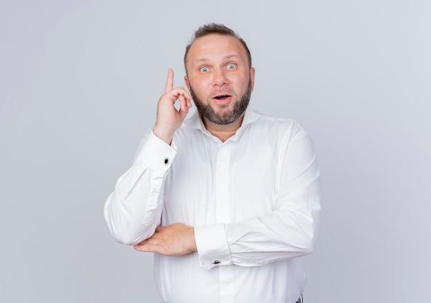 Бородатый мужчина в белой рубашке с удивлением улыбается, показывая указательный палец, имеющий отличную новую идею, стоящий над белой стеной